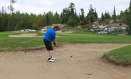 golfer hitting it out of the bunker near thunder bay