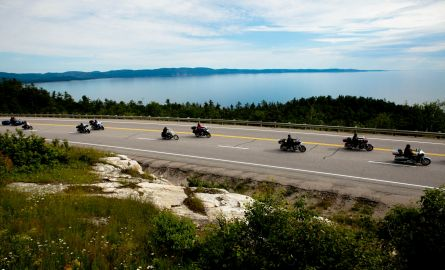A group of motorcycles riding on the shore of Lake Superior