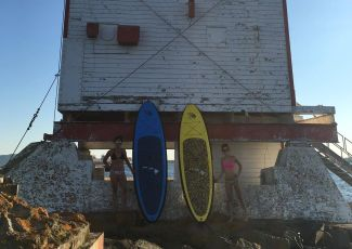 Paddleboards lean against Thunder Bay main lighthouse