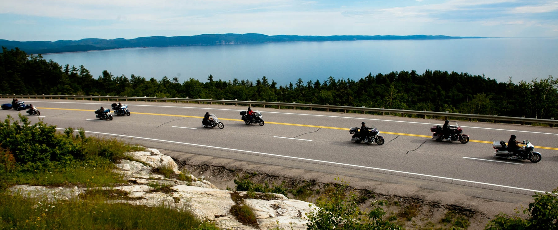 group of people on motorcycles on highway beside Lake Superior