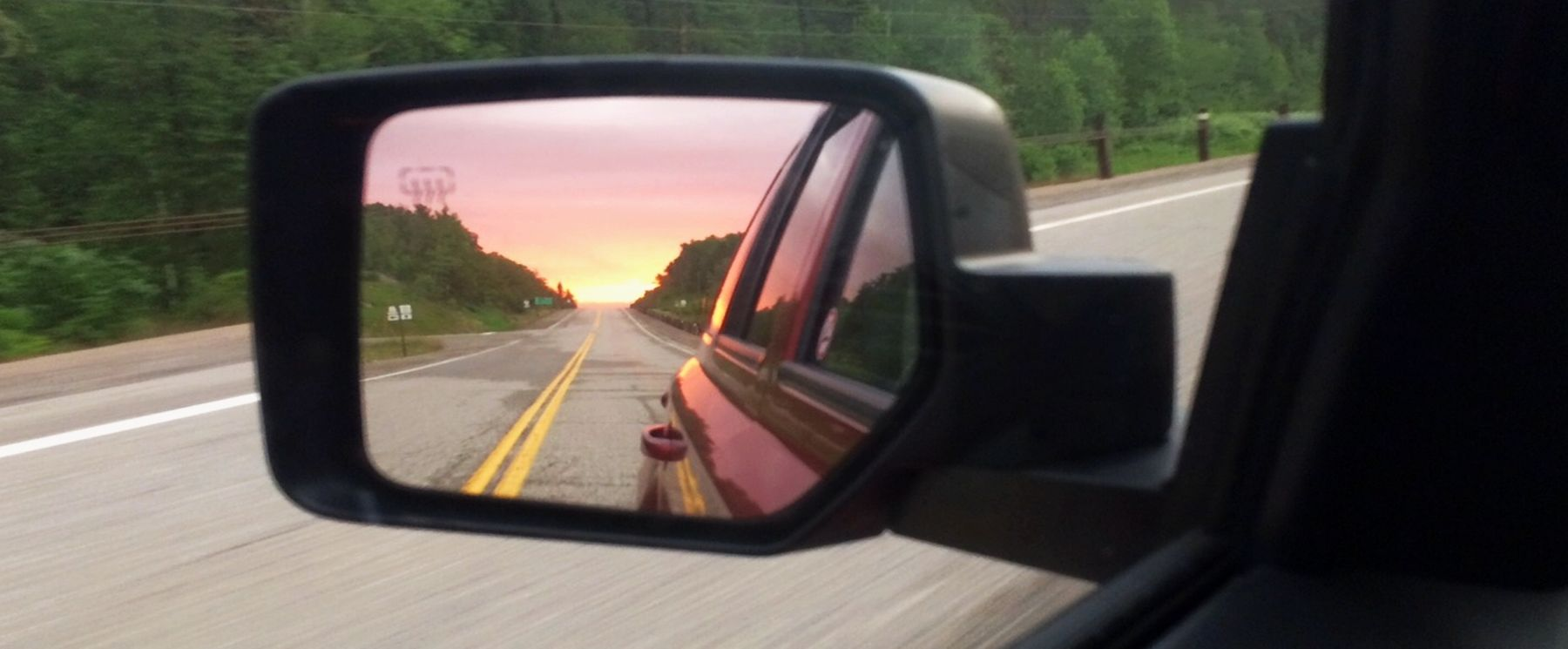 view of northern highway in a rear view mirror