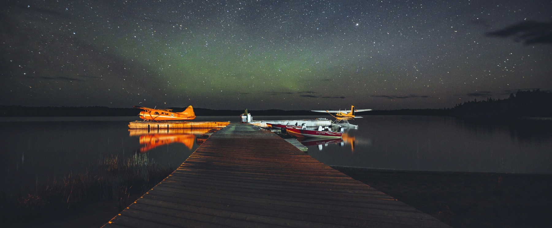 IMage of float planes at a dock under the northern lights