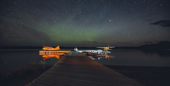 Float planes at a dock with Northern lights overhead