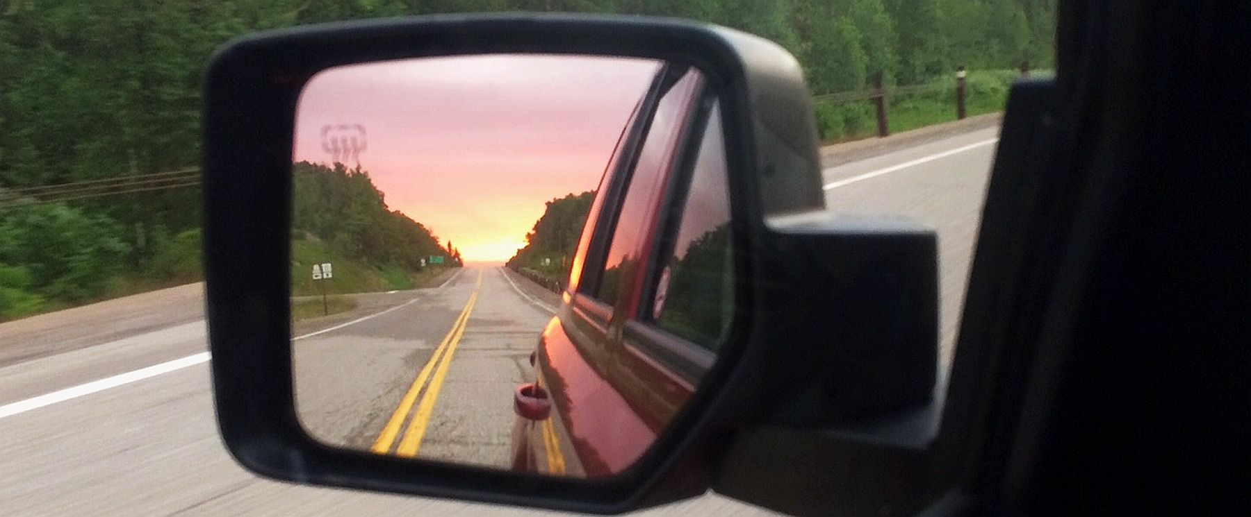 A sunset in a rearview mirror on Highway 11 near Thunder Bay